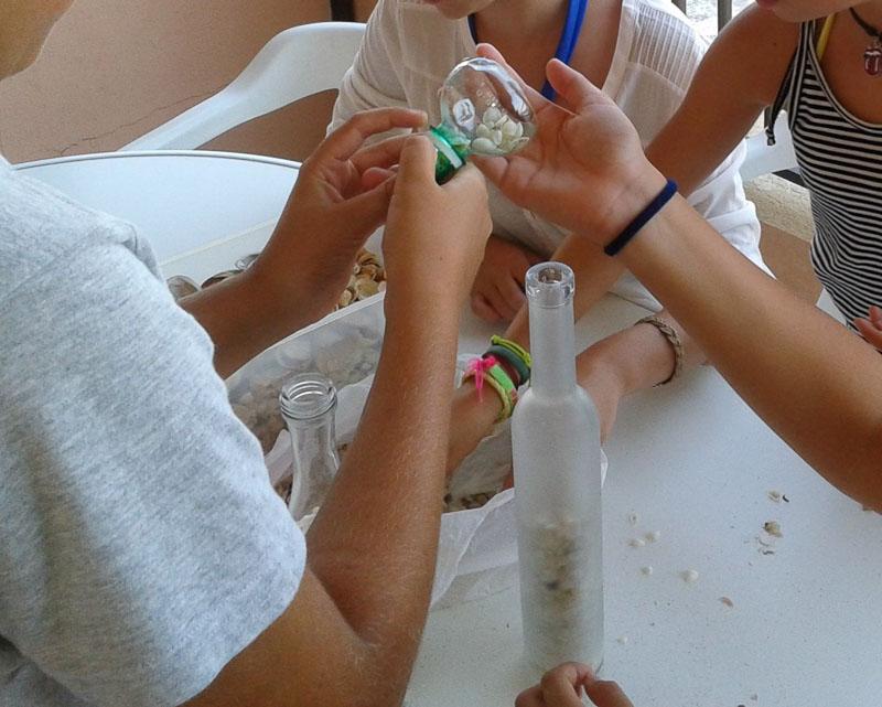 reciclando botellas de cristal con ninyos. conchas de playa embotelladas