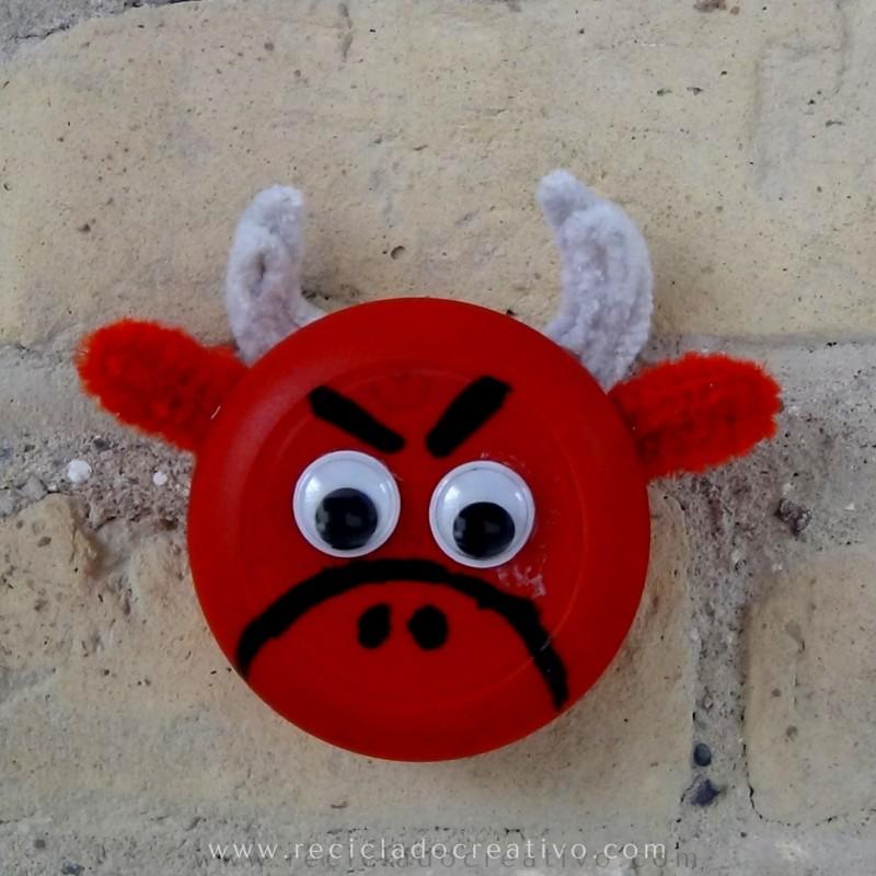 Toro rojo, una manualidad para niños hecha con un tapón de botella de color rojo.