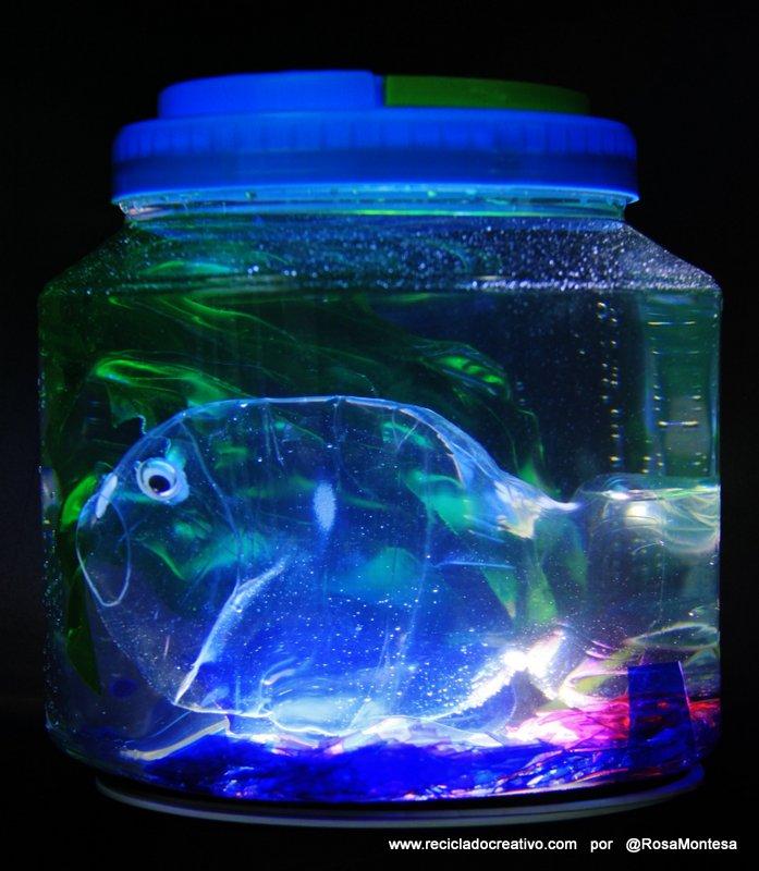 Pez hecho con una botella de plástico, dentro de una pecera con botellas de PET