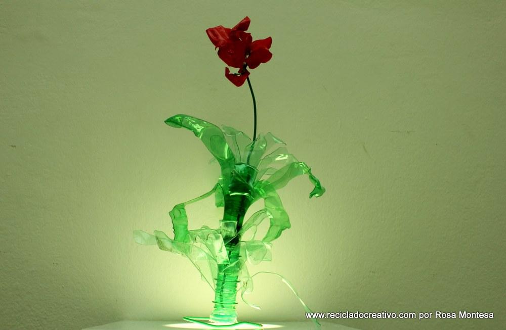 Flor de color rojo pasión con botellas de plástico