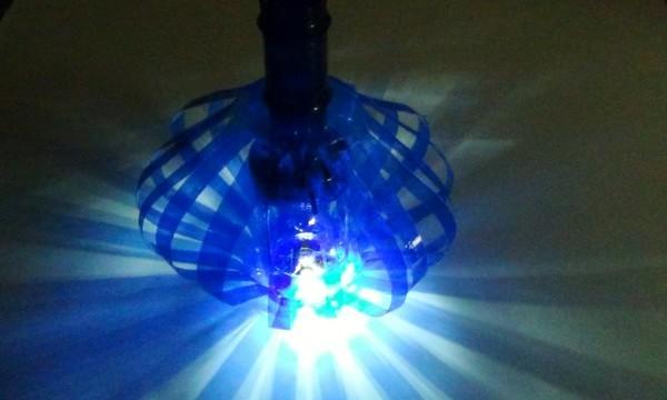 Celebrando un millón de visitas al video tutorial de la lámpara con dos botellas de plástico de color azul.